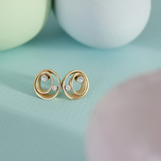 1 pair of yellow gold earrings with two wavy circles with 2 diamonds per earring