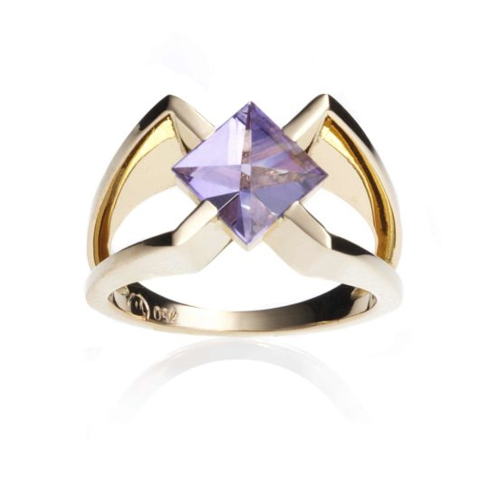 An 18 carat golden ring in a colour shade between yellow and rose gold. This ring encloses a gemstone, an amethyst, cut in Context cut.