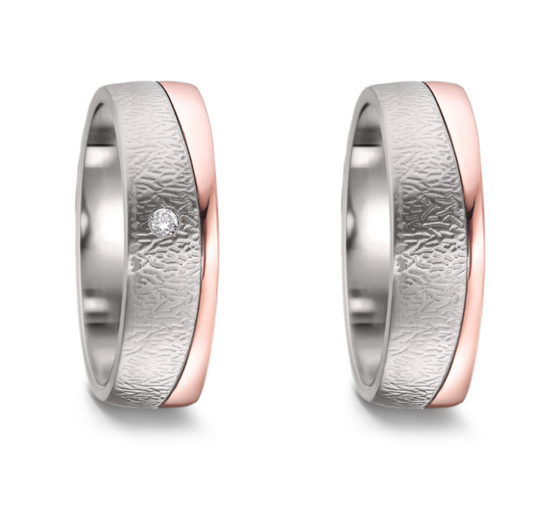 A pair of wedding or friendship rings crafted in titanium and combined with 18 karat rose gold. The ladies' model has a small diamond.